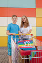 Boy and girl with shopping trolley full of purchases in the street Royalty Free Stock Images