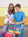 Boy and girl with shopping trolley full of purchases in the street Stock Image
