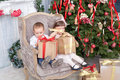 Boy and the girl sit in a chair with gifts near christmas fir tree Stock Image