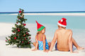 Boy and girl sitting on beach with christmas tree and hat relaxing Stock Images