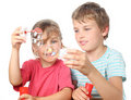 Boy and girl sitting and blowing bubbles Stock Image