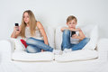 Boy and girl sitting on the couch with your phone teenagers a white sofa looking at Stock Image