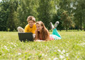 Boy and girl sitting on grass with laptop, online in park. Two smiling teenagers students with laptop resting on meadow. Education Royalty Free Stock Photo
