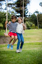 Boy and girl sitting on a swing in park Royalty Free Stock Photo