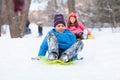 Boy and girl sliding on sledges in park.