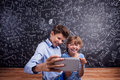 Boy and girl with smartphone taking selfie against blackboard cute smart phone at school in front of a big studio shot on black Royalty Free Stock Photo