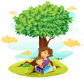 A boy and girl studying under tree Stock Images