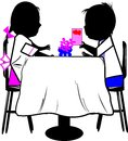 Boy and girl at table Stock Photos