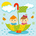 Boy and girl on the umbrella little floating in a puddle by Stock Image