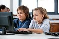 Boy and girl using desktop pc in school computer cute little at desk lab Royalty Free Stock Photography