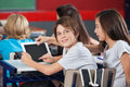Boy with girl using digital tablet at desk side view portrait of little in classroom Royalty Free Stock Image