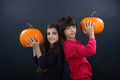 Boy and girl wearing halloween costume with pumpkin on black ba background Royalty Free Stock Image