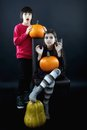 Boy and girl wearing halloween costume with pumpkin on black ba background Stock Photo