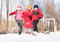 Boy and girls playing with snow in winter park spending time together outdoors Royalty Free Stock Images