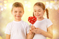Boy gives a little girl candy red lollipop in heart shape. Valentine`s day. Kids love. Royalty Free Stock Photo