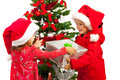 Boy giving christmas present to girl happy offering little near tree Royalty Free Stock Images