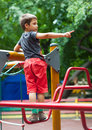 Boy giving directions climbed up on a metal structure in playground Royalty Free Stock Photos
