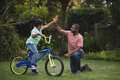 Boy giving high five to father while riding bicycle Royalty Free Stock Photo