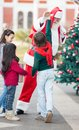 Boy giving high five to santa claus with friends in courtyard Royalty Free Stock Photos