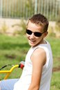 Boy in glasses on a bike outside Royalty Free Stock Image