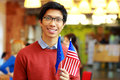 Boy in glasses holding flag of europe union and usa happy asian Stock Image