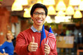 Boy in glasses holding flag of europe union with usa happy asian and showing thumb up Stock Image