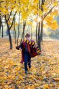 boy in glasses runs in autumn park with gold leaves, holds book in his hands