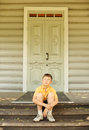 Boy in glasses seat on doorstep Royalty Free Stock Photography