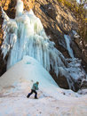 Boy goes through the snow near a waterfall Stock Photography