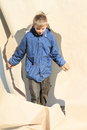 Boy going thru hole little in blue jacket and grey pants a in big paper Royalty Free Stock Photography