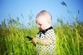 Boy in grass call by phone little green Royalty Free Stock Photography