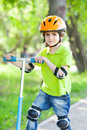 Boy in green jacket stands with kick scooter suburban park Stock Images