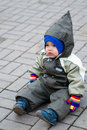 A boy in green snowsuit sitting on paving stone Royalty Free Stock Image