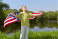 Boy green t shirt stands bank pond eyes closed against sun holds unfolded flag behind his back Stock Images