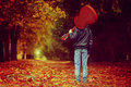 Boy with guitar walking on the autumn road. Back view. Royalty Free Stock Photo