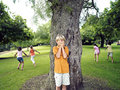 Boy with hands covering eyes playing hide and seek in park hiding from friends behind tree Royalty Free Stock Photo