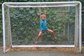 Boy is hanging on framework of goal Royalty Free Stock Photo