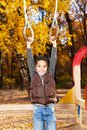 Boy hanging on the rings years old black in playground in autumn park Stock Photo