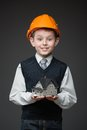 Boy in hard hat keeping house model portrait of on grey background Royalty Free Stock Image