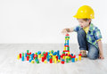 Kids Play Room, Child in Hard Hat Playing Building Blocks Toys Royalty Free Stock Photo