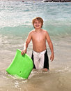 Boy has fun at the beach with surfboard Stock Photography