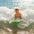 Boy has fun playing in the waves of the ocean with surfboard at beach Stock Image