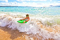 Boy has fun with the surfboard at beach Stock Photos