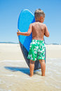 Boy has fun with the surfboard little surfer back view of standing near ocean Stock Photography
