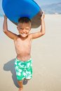 Boy has fun with the surfboard little surfer runing near ocean Royalty Free Stock Photo