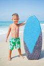 Boy has fun with the surfboard little surfer standing near ocean Royalty Free Stock Photos