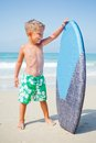 Boy has fun with the surfboard little surfer standing near ocean Stock Image
