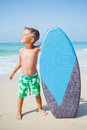 Boy has fun with the surfboard little surfer standing near ocean Stock Photo