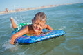 Boy has fun with the surfboard on in transparency sea Stock Photography