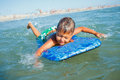 Boy has fun with the surfboard on in transparency sea Stock Photos